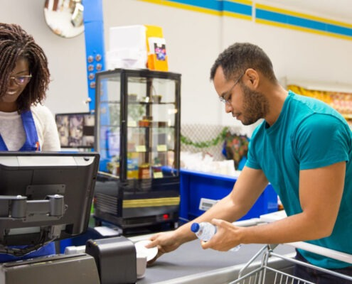 Female cashier reading barcodes at cash register. Male customer in casual putting products from cart to cashier counter. Payment in supermarket concept